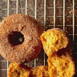 Baked Pumpkin Doughnuts! This recipe makes the softest, warmest, and most perfectly cinnamon-spiced pumpkin donuts with cinnamon sugar coating. They're just over 100 calories each, too!
