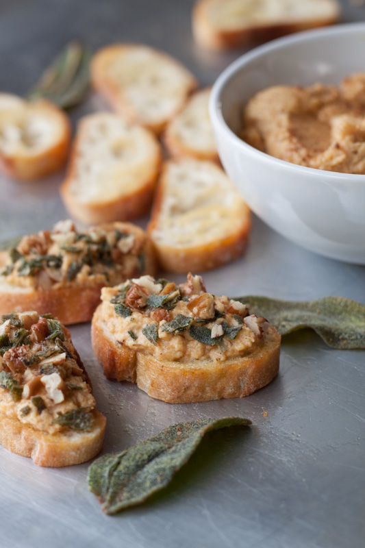 Spiced Autumn Crostini - a perfect fall appetizer or holiday appetizer! From Seriously Delish cookbook by Jessica Merchant, this crostini recipe is topped with mascarpone and pumpkin, fried sage, and toasted nuts!