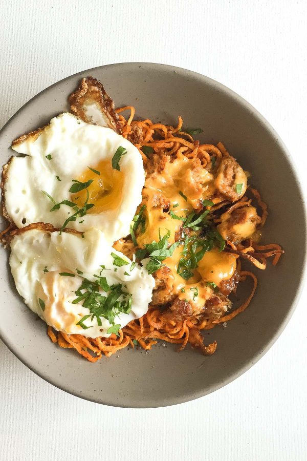 Healthy Sausage Egg and Cheese Breakfast Bowl with Curly Sweet Potato Fries - Make curly baked shoe string sweet potato fries with a spiralizer, and use those as the base for a breakfast bowl with fried eggs, crumbled breakfast sausage, and cheddar cheese!