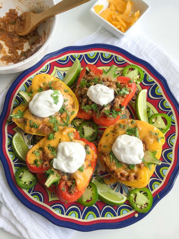Healthy Veggie Loaded Mexican Stuffed Peppers Recipe - with ground turkey, mushrooms, peppers, onions, and cheddar! There are no grains inside, making this a low carb recipe! Everyone LOVES this filling, super flavorful taco-seasoned stuffed pepper. 374 calories for 2 big pepper halves | andiemitchell.com
