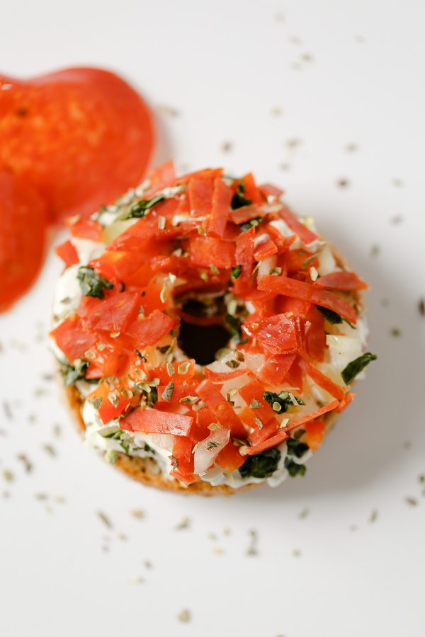Pizza Bagel! 5 Delicious and Light Bagel Toppings - here are 5 delicious bagel spreads you can make with no guilt at all! These toppings include flavors like funfetti, pizza, mediterranean, blueberry coconut, and even chocolate peanut butter banana! All have nutrition information!
