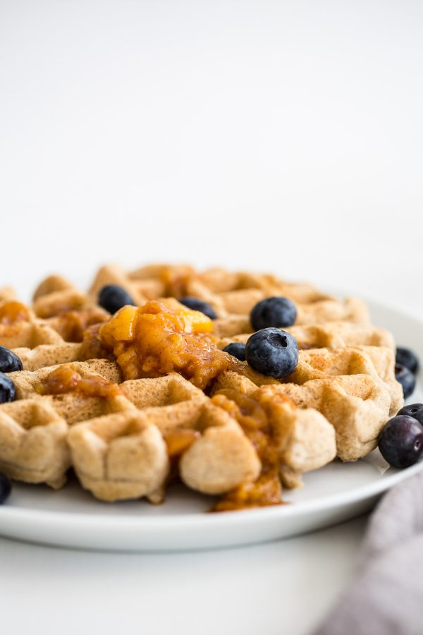 Whole Wheat Waffle Recipe with Warm Peach Sauce - these whole grain waffles are deliciously fluffy and light thanks to whipped egg whites in the batter! A homemade peach sauce makes them the perfect weekend brunch, but they're also freezer-friendly for easy weekday breakfasts!