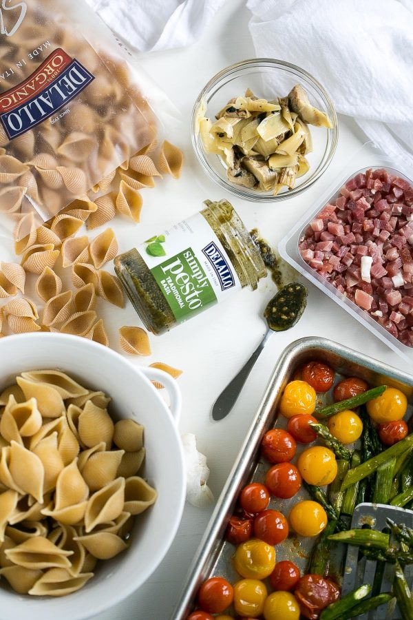 Whole Wheat Pasta Salad with Pesto, Asparagus and Roasted Tomatoes - A flavor-packed pasta salad can be easy and healthy, too, and this recipe is proof. Slather DeLallo whole wheat shells in basil pesto, then toss them with roasted asparagus, sweet blistered tomatoes, charred artichokes, and salty bits of prosciutto. All this for only 249 calories per serving