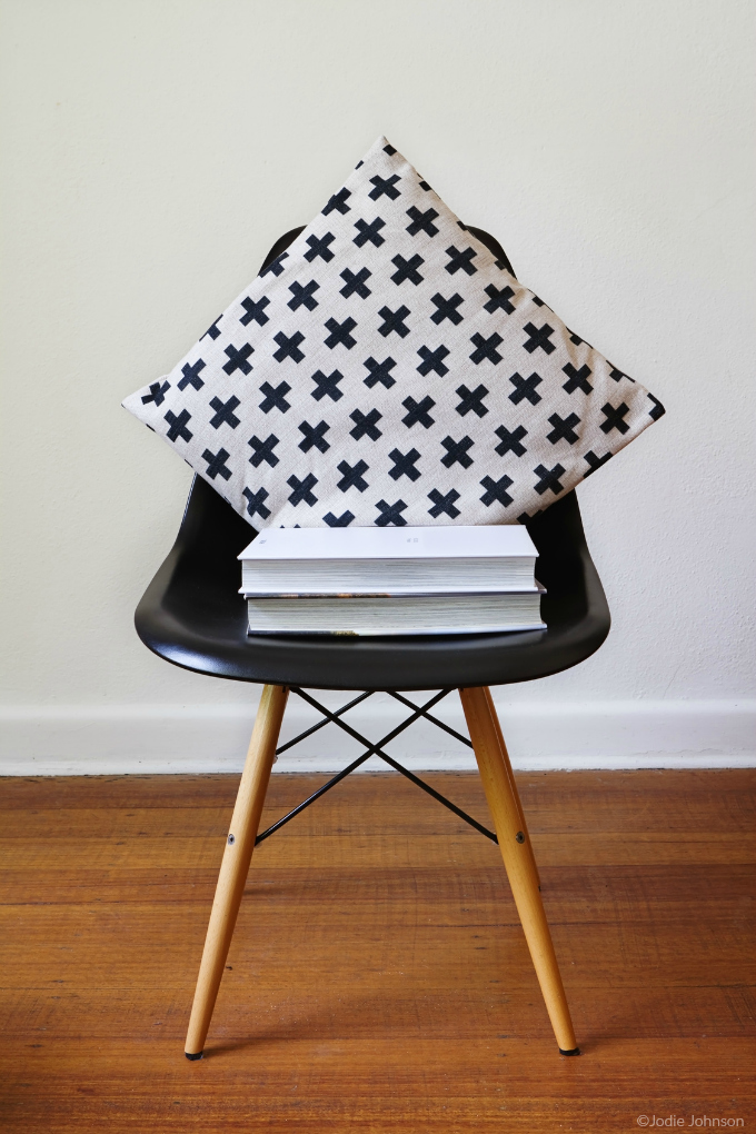 Black chair with black and white pillow and stack of books - photo copyright Jodie Johnson