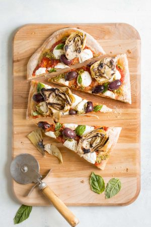 Grilled Artichoke, Olive and Pesto Flatbread Recipe - It's lighter than pizza (423 calories) and makes a better appetizer, too! Topped with kalamata olives, grilled artichokes, basil pesto, and mozzarella