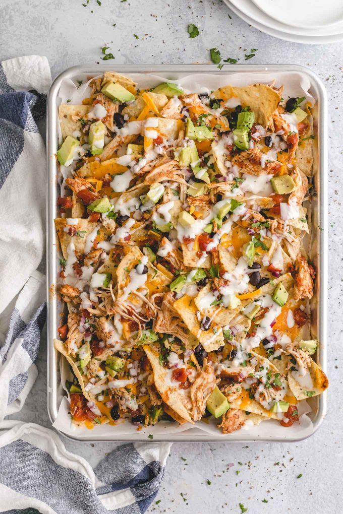 The Best Lighter Chicken Nachos! 396 calories or 8 WW points. Piled high with crisp tortilla chips, delicious and easy slow cooker Mexican shredded chicken, seasoned black beans, melted cheddar cheese, and all the fixins!