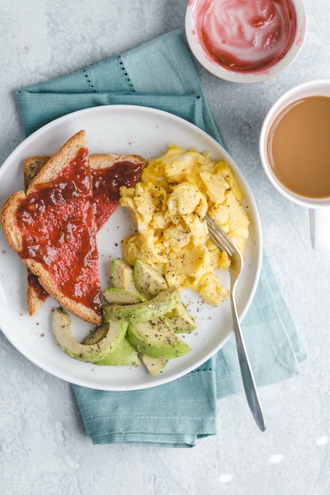 breakfast of scrambled eggs, toast with jam, avocado