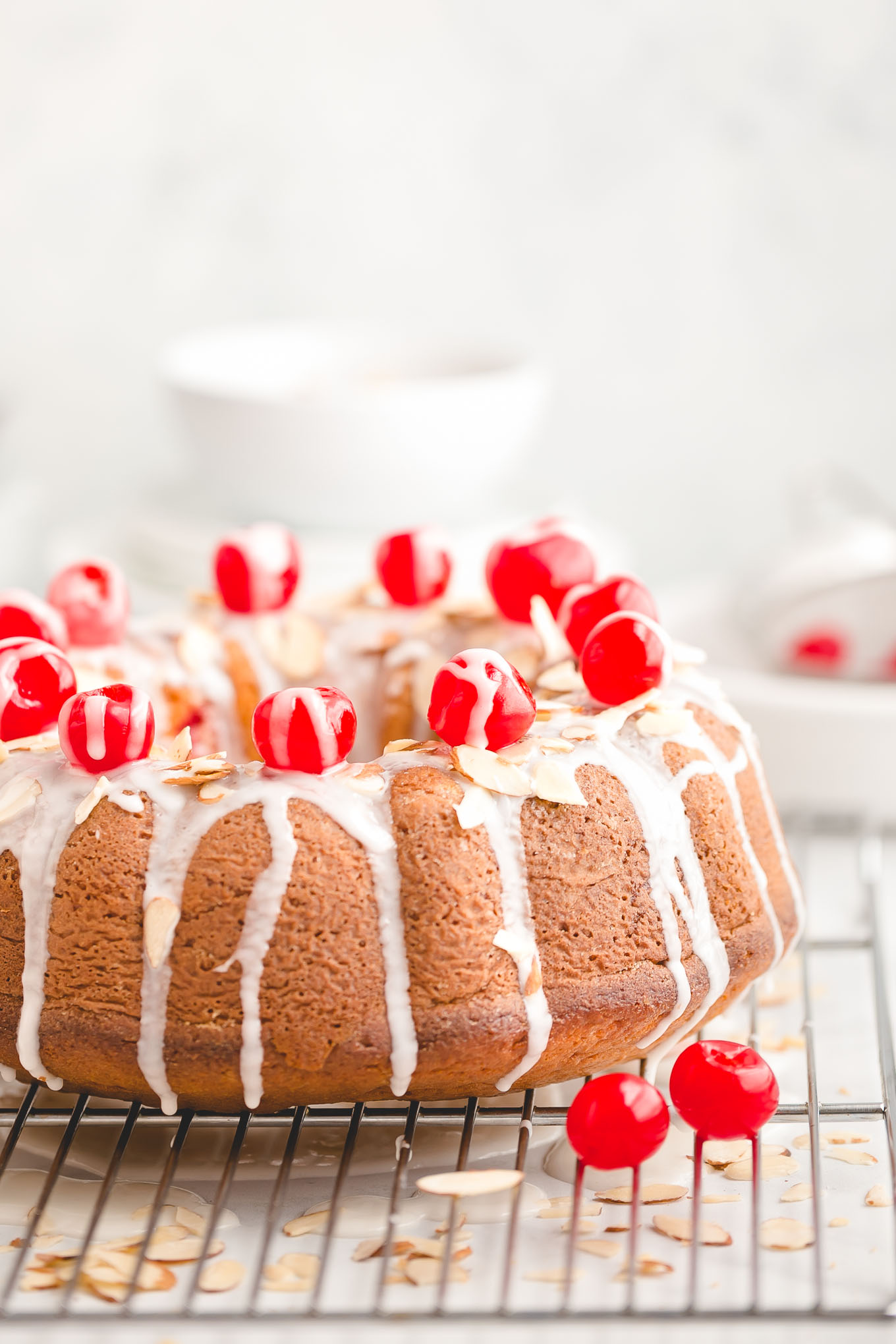 Easy Cherry Almond Bundt Cake - Made with yellow cake mix, instant vanilla pudding mix, almond extract, a jar of maraschino cherries, and sliced almonds, this easy bundt cake recipe is full of irresistible cherry almond flavor and effortlessly soft and tender.